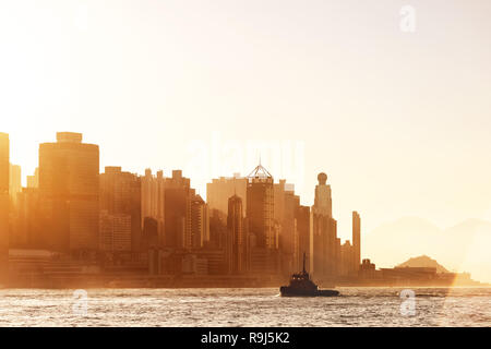 Silhouettes of Hong Kong skyscrapers against sunset sun - Stock Image