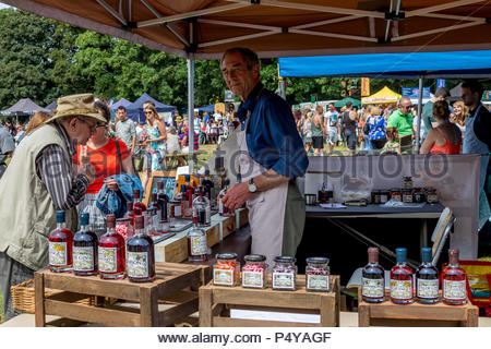 Visitors enjoying the sunshine at Fleet Food Festival 2018. A customers samples one of and extensive range of liqueurs. - Stock Image