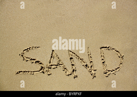'Sand' written out in wet sand. Please see my collection for more similar photos. - Stock Image