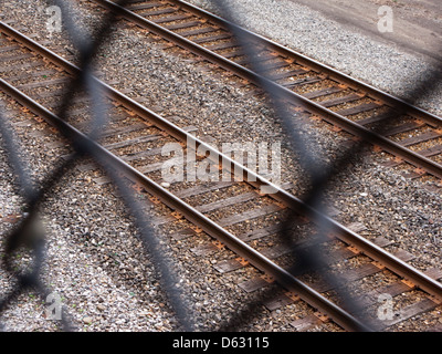 looking at railroad tracks through chain-link fence - Stock Image