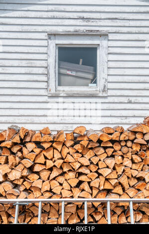 A pile of split logs stacked beside a house in Newfoundland ready for the winter. - Stock Image