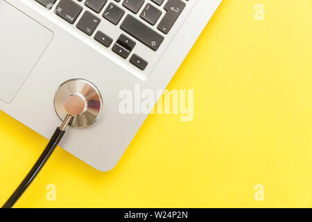 Stethoscope keyboard laptop computer isolated on yellow background. Modern medical Information technology and sofware advances concept. Computer and g - Stock Image