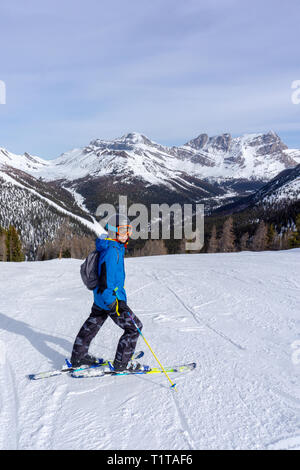 Young skier at the top of a mountain range in Lake Louise in the Canadian Rockies of Alberta, Canada. - Stock Image