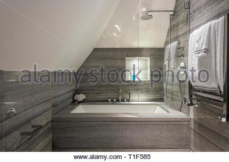 Bathtub with overhead shower in gray tiled bathroom - Stock Image