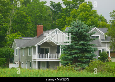 Timber house in the countryside surrounded by green vegetation in Michigan, United States. - Stock Image