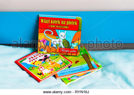 Poznan, Poland - November 18, 2018: Colorful child book about cat on a blue bed. - Stock Image