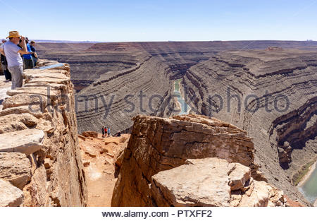 Visitors enjoy the view of the 1,000 foot deep meander of the San Juan River at Goosenecks State Park near Mexican Hat, Utah USA - Stock Image