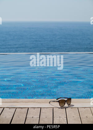 Sunglasses on wooden decking by an infinity pool - Stock Image