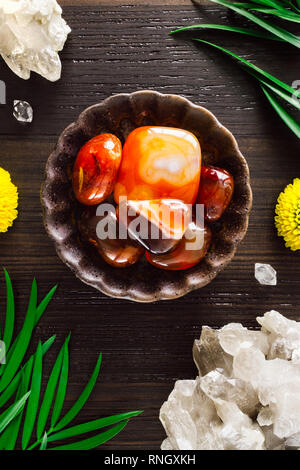 Carnelian with Smoky Quartz and Mums on Dark Wood - Stock Image
