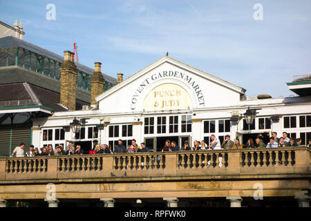 People men and women watching a street performer from the balcony of the Punch and Judy tavern inn pub in London's Covent  Garden London - Stock Image