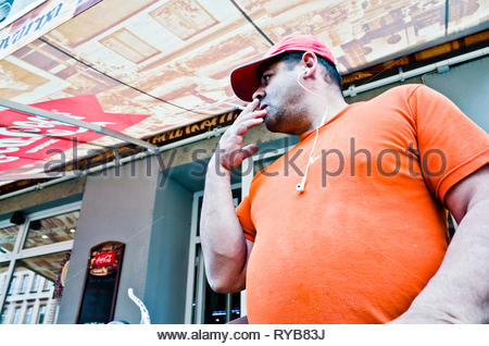 man with baseball hat smoking a cigarette in the street - Stock Image