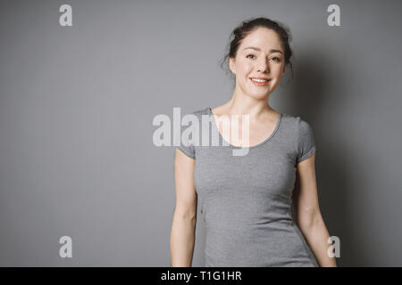 happy young woman with bright face and beaming smile against gray background with copy space - Stock Image