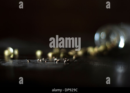 Cardamom seeds next to pods spilling from glass jar onto a dark wood table top surface in a low light - Stock Image