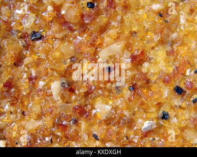 Lot of small amber pieces glued on clothe for background - Stock Image