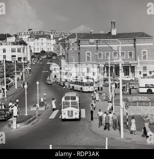 1950s, historical, Bournemouth, England, UK. Seen in the picture, local buses, people and the Swimming and Turkish Baths, featuriing 'Aquafantasia', every Wednesday. Also seen the builing of Hants & Dorset Motor Services. - Stock Image