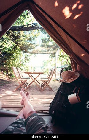 vertical view of crossed legs of a hiker man resting barefoot in a camping tent, travel discovery concept, point of view shot - Stock Image