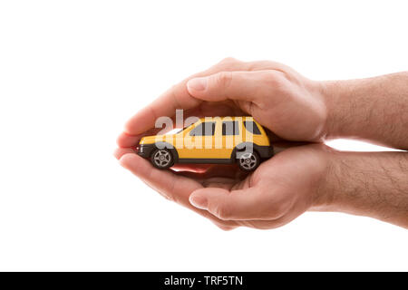 Car protection. Small yellow car covered by hands isolated on white background with clipping path - Stock Image
