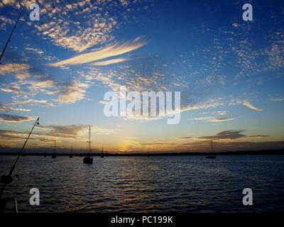 A spectacular inspirational brightly coloured atmospheric cloudy sky cloudscape featuring an Altocumulus & Cirrus cloud formation in a mid blue sky. - Stock Image