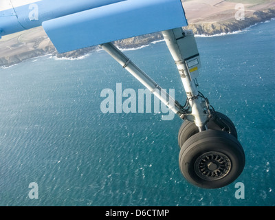 Landing gear of plane on its approach to landing,over the sea.It is a Flybe plane landing in the Isle of Man.Sunny,rippled - Stock Image