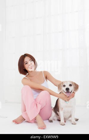 Young woman sitting with dog and smiling at the camera, - Stock Image