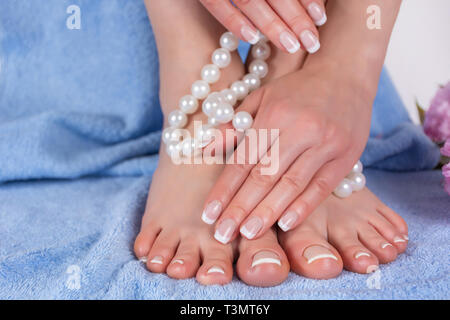 Beautiful bare feet and hands with french manicure and pedicure in spa salon on blue blue towel with decorative flower and pearls. Spa and recreation - Stock Image