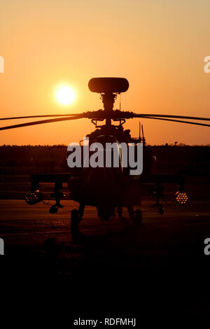 Army Air Corps Apache AH1 attach helicopter silhouetted against the setting sun as it sits at Woodbridge airfield whilst deployed on exercise. - Stock Image