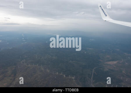Passenger jet flying over a wind farm - Stock Image