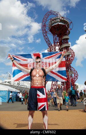 Man with Union Jack flag standing in front of Orbit sculpture tower designed by Anish Kapoor on a sunny day at Olympic - Stock Image