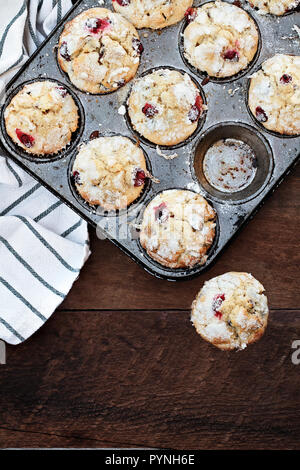 Cranberry Muffins  in a muffin tin with kitchen towel over a rustic wood  background. Free space for text. - Stock Image