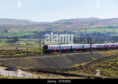 Class 350 electric multiple unit (emu) passenger train operated by FirstTransPennine Express, passing Tebay as it ascends Shap on March 25th 2017, hea - Stock Image
