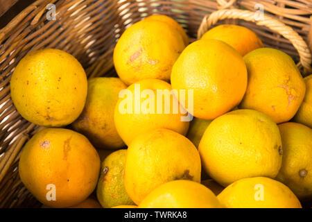 View over oranges in handmade wicker basket - Stock Image
