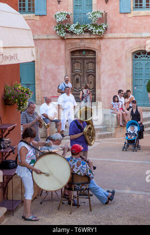 Group of musicians perform traditional French songs in front of the Marie de Roussillon, Roussillon, Provence, France - Stock Image