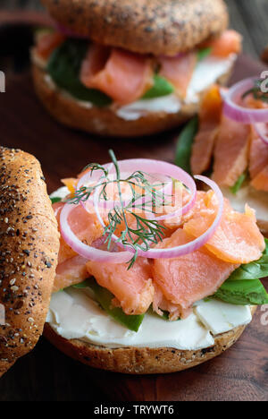 Lox - Everything bagel with smoked salmon, spinach, red onions, avocado and cream cheese over a rustic wood table background. Selective focus with blu - Stock Image