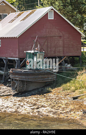 A mini tugboat tied up against an old wooden boathouse along Hammer Slough in Petersburg, Mitkof Island, Alaska. Petersburg settled by Norwegian immigrant Peter Buschmann is known as Little Norway due to the high percentage of people of Scandinavian origin. - Stock Image