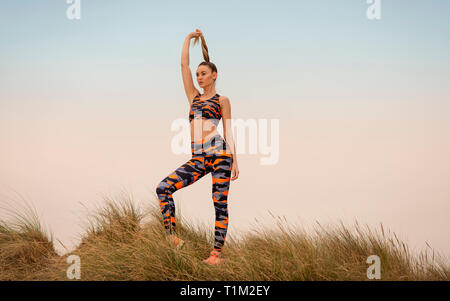 sporty woman holding her ponytail, sports concept - Stock Image