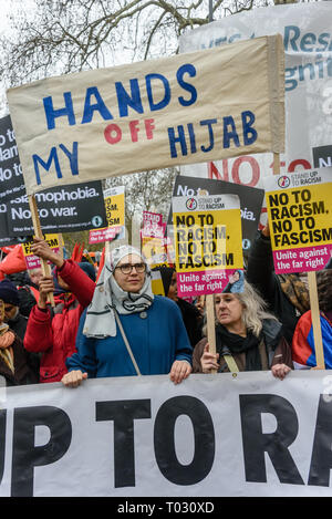 London, UK. 16th March 2019. A  banner 'Hands Off My Hijab'.  Thousands march through London on UN Anti-Racism day to say 'No to Racism, No to Fascism' and that 'Refugees Are Welcome Here', to show solidarity with the victims of racist attacks including yesterdays Christchurch mosque attack and to oppose Islamophobic hate crimes and racist policies in the UK and elsewhere. The marchers met in Park Lane where there were a number of speeches before marching to a rally in Whitehall. Marches took place in other cities around the world including Glasgow and Cardiff. Peter Marshall/Alamy Live News - Stock Image