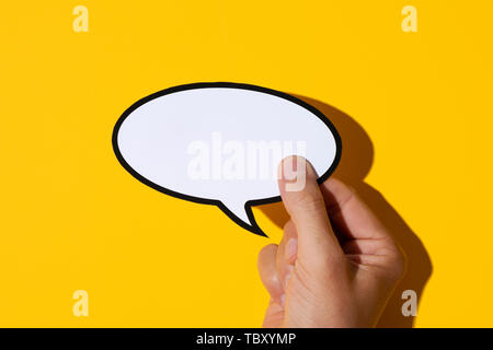 closeup of the hand of a young caucasian man holding a blank speech balloon against a yellow background, with a hard shadow - Stock Image