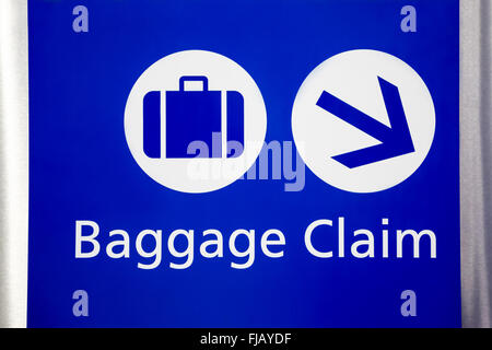 Blue airport baggage claim sign with suitcase and arrow symbols. - Stock Image
