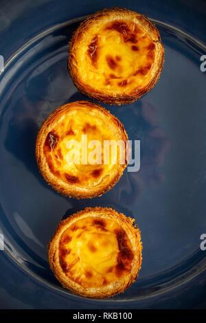 Lay Flat Image Of Three Pastel de Natas (Pastéis de Belém), On A Blue Earthenware Plate Background Portuguese Custard Tarts - Stock Image