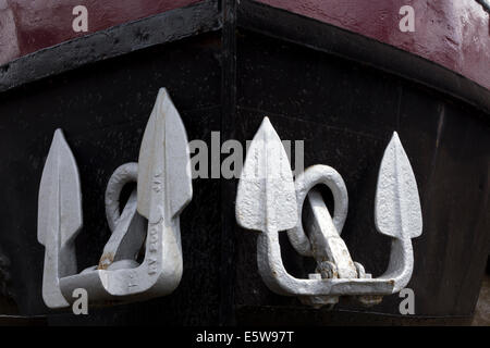 Close up of boat's anchors. White / silver anchors on black hull. - Stock Image