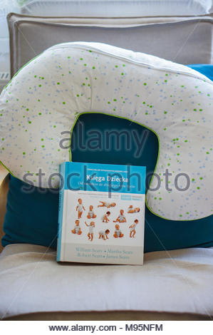 Poznan, Poland - March 18, 2018: Polish baby information book and feeding pillow on a chair - Stock Image