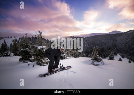 Man wearing ski on snowy mountain against sky - Stock Image