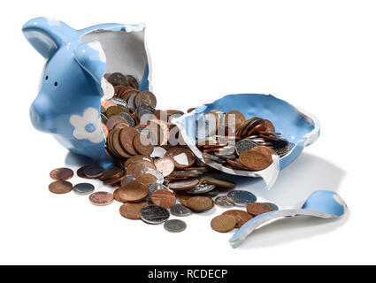 A smashed blue piggy bank with UK sterling coins spilling out - Stock Image