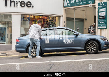 Man takes Uber taxi cab minicab ride on a UK street. - Stock Image