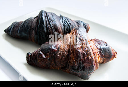two burnt croissants on a plate - Stock Image