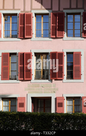 Details of old medieval style building. The building has pink concrete walls and the window frames are white and red and made of wood. - Stock Image