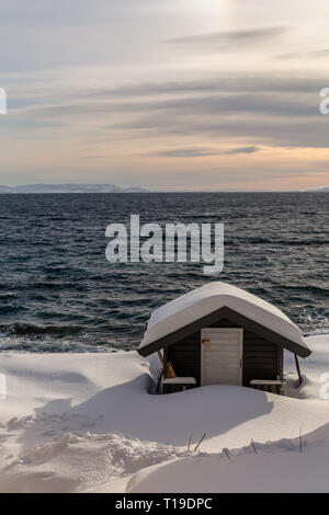 A small snow covered wooden building in the port town of Honningsvag in Norway. - Stock Image