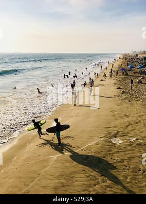 Beach goers play in the water during a hot summer day. Manhattan Beach, California USA. - Stock Image