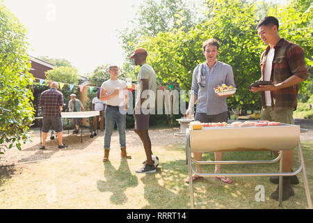 Male friends barbecuing in sunny summer backyard - Stock Image