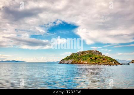 Touristic rabbit island, calm sea, sky and clouds in Bodrum, Gumusluk, Mugla, Turkey - Stock Image